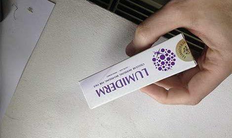 Упаковка крема Люмидерм в руках